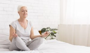 Young woman meditating sitting in lotus position on bed